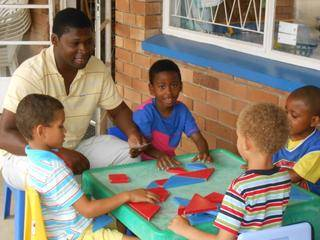 Daddy Bandile shows Milani and the other boys how to use instructions with the 3D-blocks.