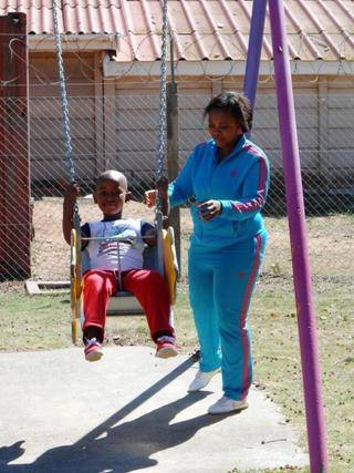 Mom Nontobeko is pushing Olwam on the Noddy swing.